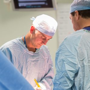 Surgeon operating on patient in operating theatre