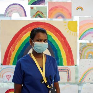 Nurse stands in front of pictures of rainbows