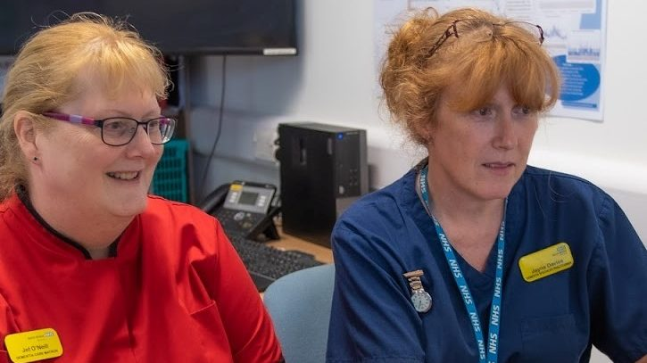 Two female staff members working together at a computer